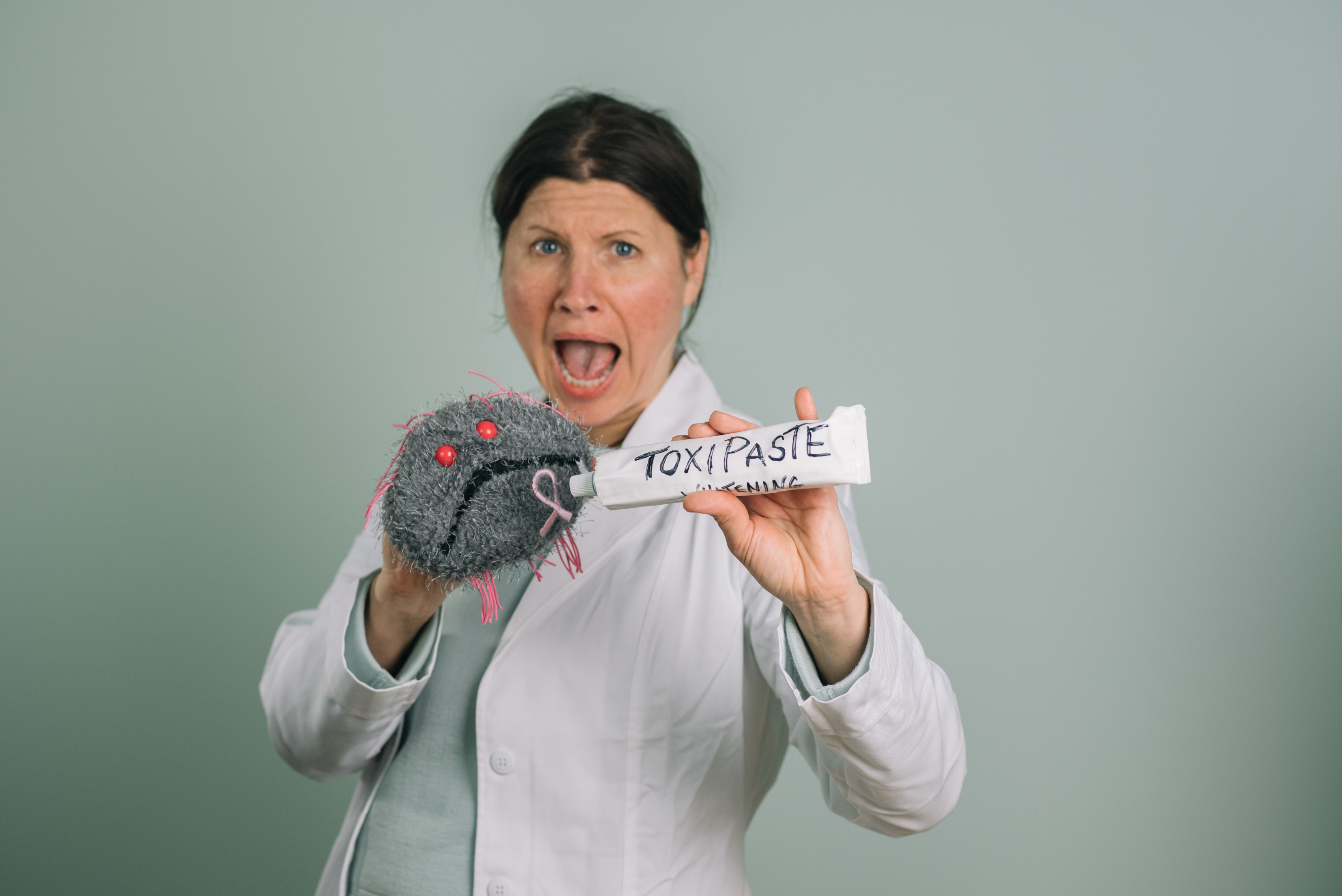 "Trina holding a tube of ""toxipaste"" and a stuffed cancer cell"